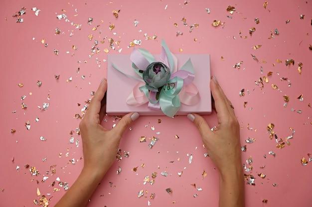 Caixa de presente bonita em rosa festivo nas mãos femininas
