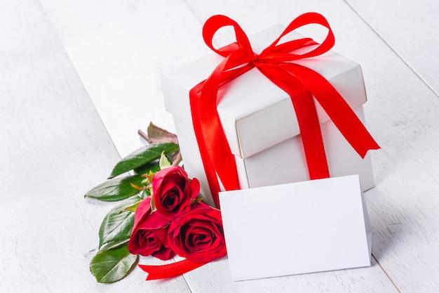 Caixa de presente branca amarrada com fita vermelha e rosas na mesa de madeira