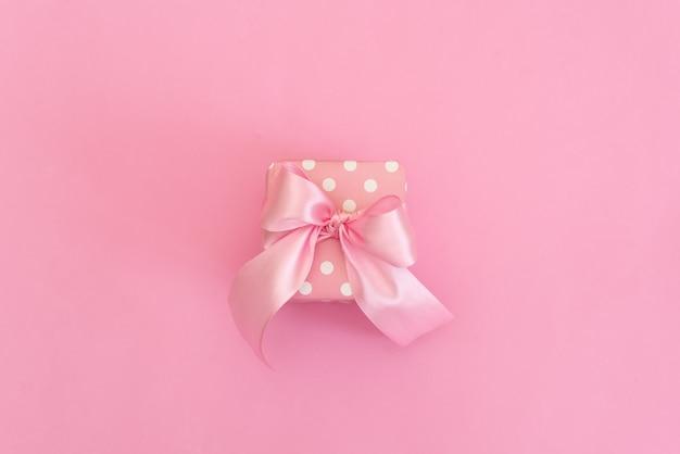 Caixa de presente branca com a fita azul no fundo cor-de-rosa para o espaço da cópia.