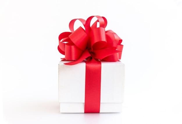 Caixa de presente branca com arco de fita vermelha no fundo branco