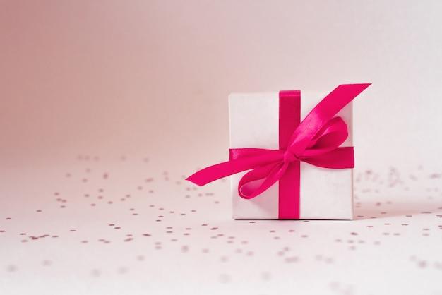 Caixa de presente branca com fita de cetim rosa.
