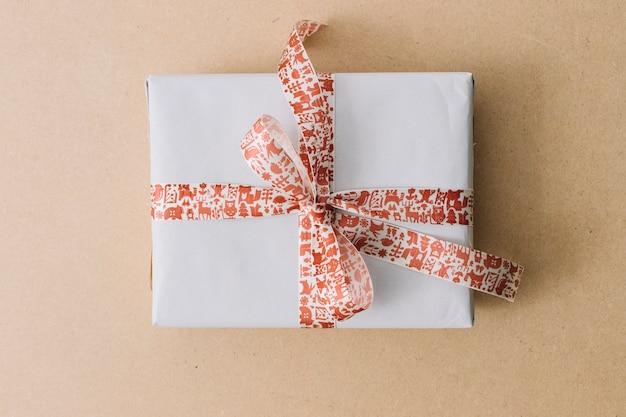 Caixa de presente branca com fita na mesa marrom
