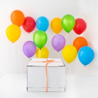 Caixa de presente branca com fita vermelha e balão colorido