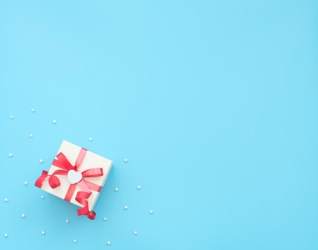 Caixa de presente branca com fita vermelha e coração branco. estilo liso