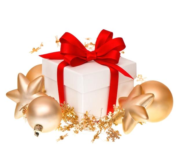 Caixa de presente branca com fita vermelha e decoração de bolas douradas em fundo branco