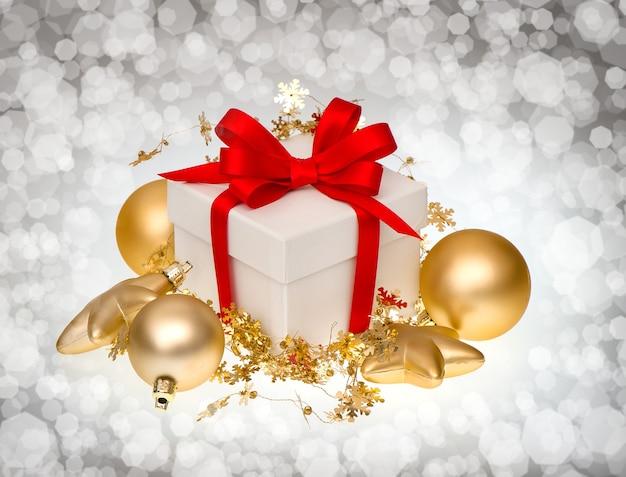 Caixa de presente branca com fita vermelha e decoração de bolas douradas sobre fundo escuro e desfocado