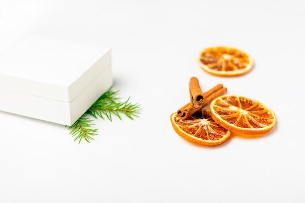 Caixa de presente branca com frutas secas de laranja e pau de canela no fundo branco