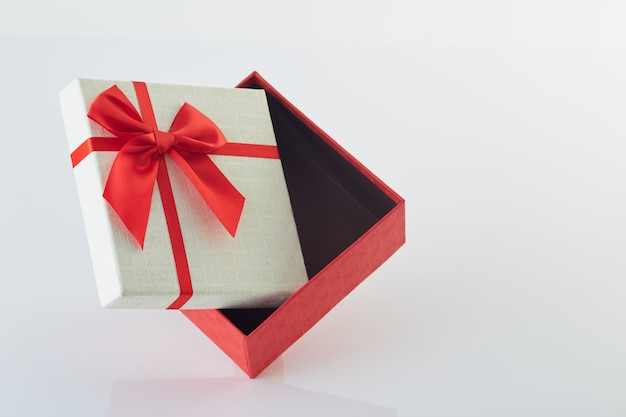 Caixa de presente branca com laço de fita vermelha no branco
