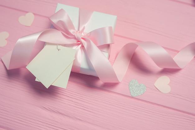 Caixa de presente branca com um laço de cetim rosa e fita na mesa rosa