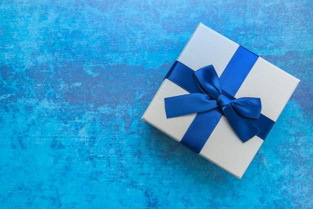 Caixa de presente branca e azul com a fita azul no fundo azul, vista superior. presentes, celebração, tema dos namorados