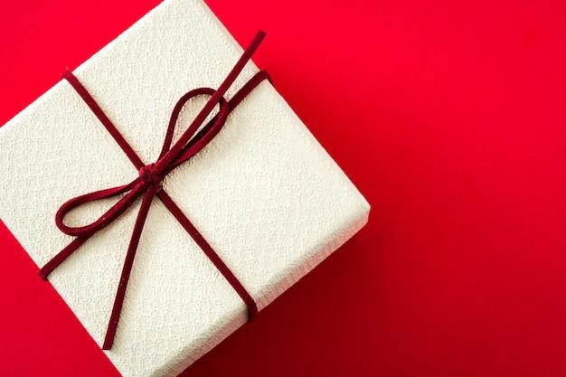 Caixa de presente branca em fundo vermelho com espaço de cópia