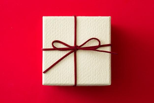 Caixa de presente branca em fundo vermelho
