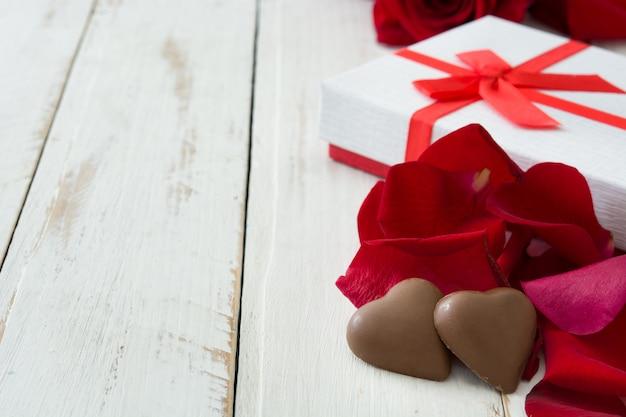 Caixa de presente branca, rosas e chocolate com forma de coração na mesa de madeira copyspace