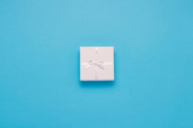 Caixa de presente branca sobre um fundo azul. estilo minimalista. vista plana, vista superior