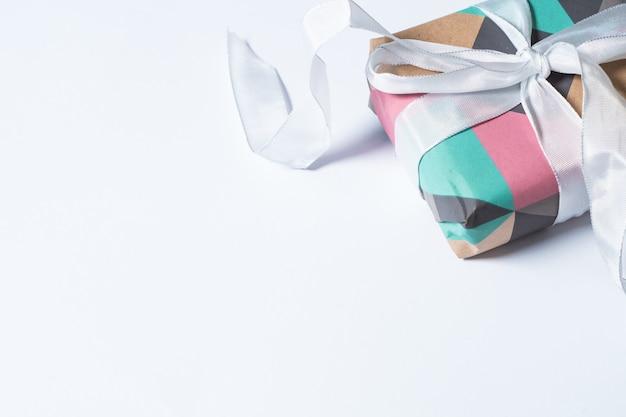 Caixa de presente colorida com uma fita branca isolada em um fundo branco