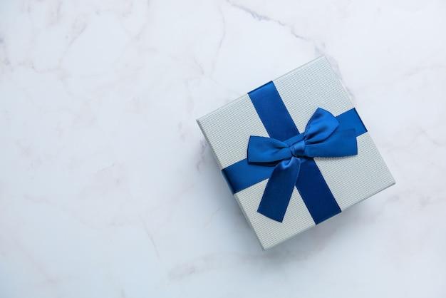 Caixa de presente com a fita azul no fundo de mármore branco, vista superior. presentes, celebração, tema dos namorados