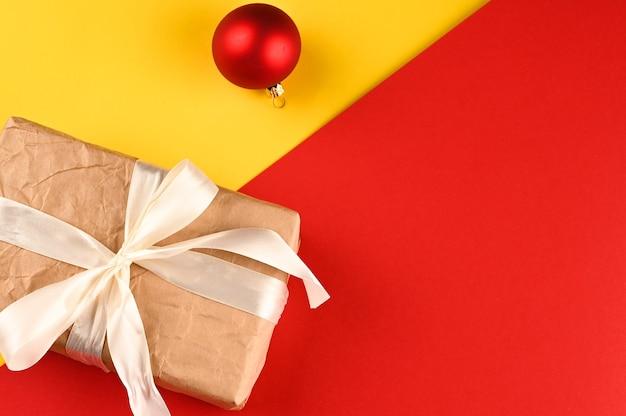 Caixa de presente com arco de luz e bola de natal em fundo vermelho-amarelo.