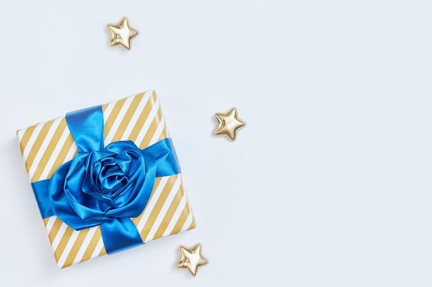 Caixa de presente com arcos azuis clássicos. invólucro listrado, estrelas douradas sobre um fundo branco. flatlay.