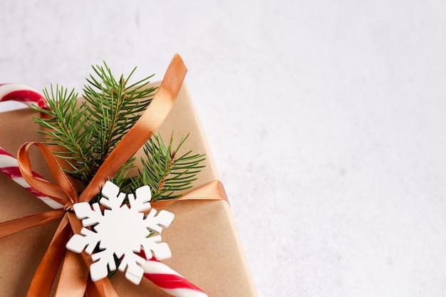 Caixa de presente com bastão de doces, laço dourado e floco de neve de madeira no fundo branco, espaço de cópia