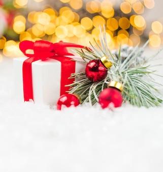 Caixa de presente com bolas vermelhas de fita vermelha na neve no fundo da árvore de natal borrada