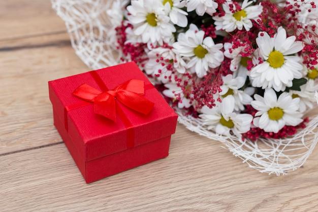 Caixa de presente com buquê de flores na mesa