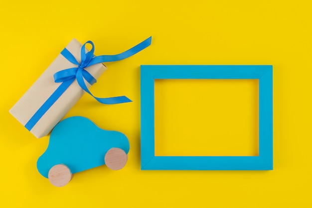 Caixa de presente com carro de brinquedo e moldura na mesa
