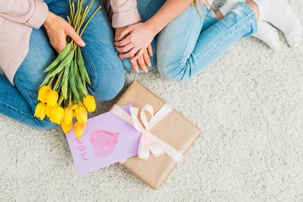 Caixa de presente com cartão postal de dia das mães perto de mulher e menina