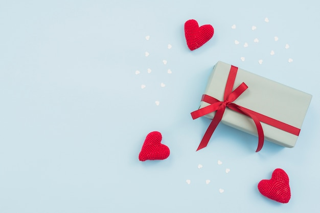 Caixa de presente com corações de brinquedo vermelho na mesa
