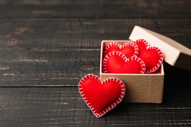 Caixa de presente com corações de feltro vermelho para dia dos namorados