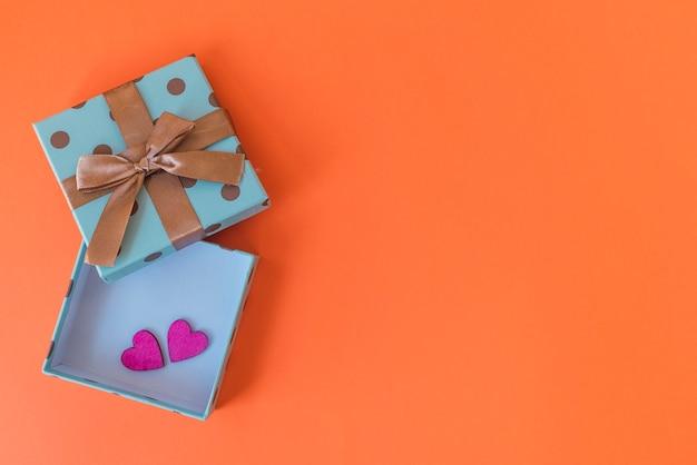 Caixa de presente com corações em fundo laranja