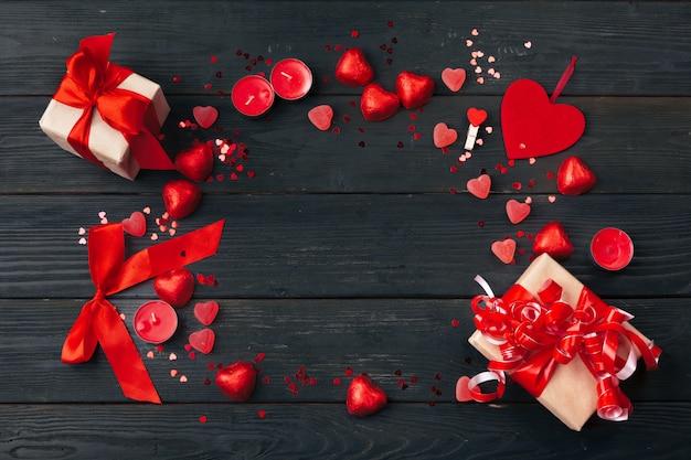 Caixa de presente com corações vermelhos na mesa de madeira
