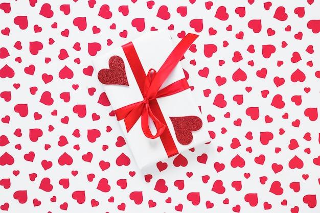 Caixa de presente com corações vermelhos na mesa