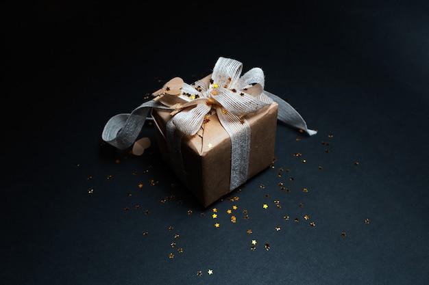 Caixa de presente com decoração ecológica na superfície de cor preta