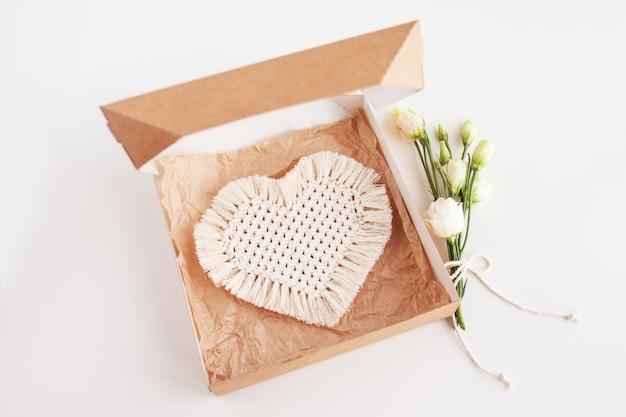 Caixa de presente com decoração macramé na superfície branca. materiais naturais, fios de algodão. eco decorações, ornamentos, decoração feita à mão. coração - símbolo de férias.