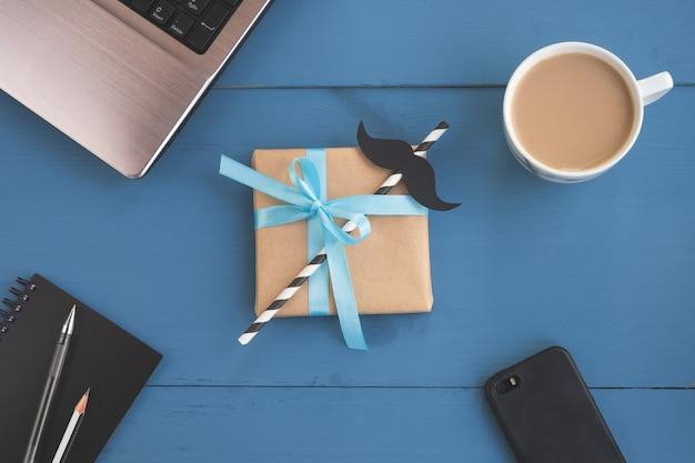 Caixa de presente com detalhe de bigode, café e laptop em fundo azul