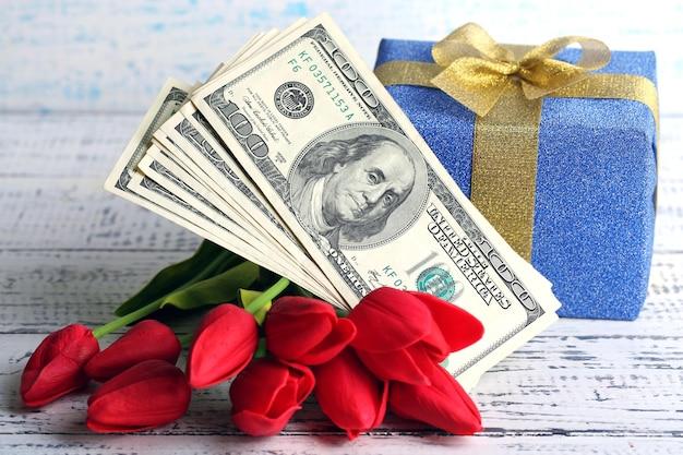 Caixa de presente com dinheiro e flores na mesa de madeira colorida