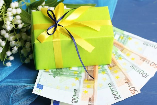 Caixa de presente com dinheiro e flores na superfície de madeira colorida
