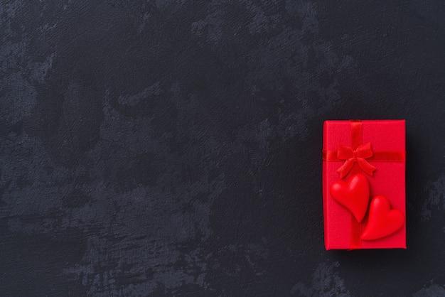 Caixa de presente com e coração de dois vermelhos no fundo preto, vista superior.