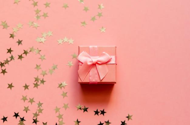 Caixa de presente com estrelas douradas holográficas.