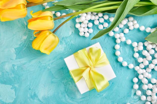 Caixa de presente com fita amarela perto de tulipa
