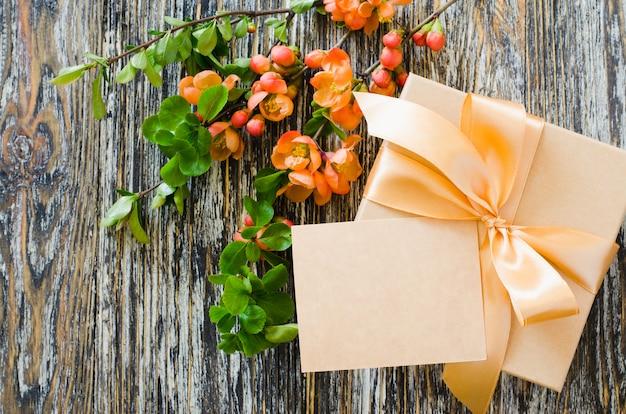 Caixa de presente com fita curva, tag em branco e ramo de floração delicado.