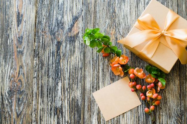 Caixa de presente com fita de laço, etiqueta em branco e delicado ramo de flores.