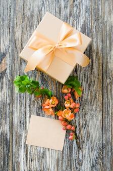 Caixa de presente com fita de laço, tag em branco e delicado ramo de flores.