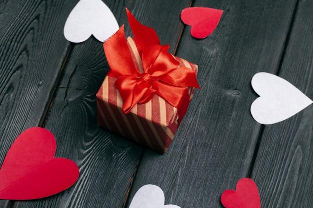 Caixa de presente com fita de laço vermelho e corações de papel para dia dos namorados