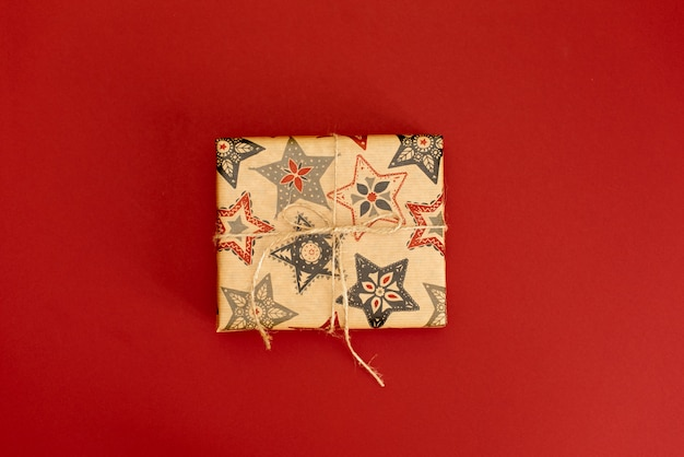 Caixa de presente com fita dourada em fundo vermelho