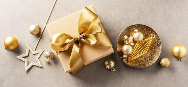 Caixa de presente com fita dourada sobre fundo cinza