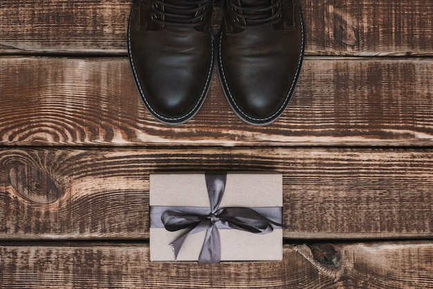 Caixa de presente com fita e sapatos de couro masculino em uma mesa de madeira. dia dos pais. presente para um homem. postura plana.
