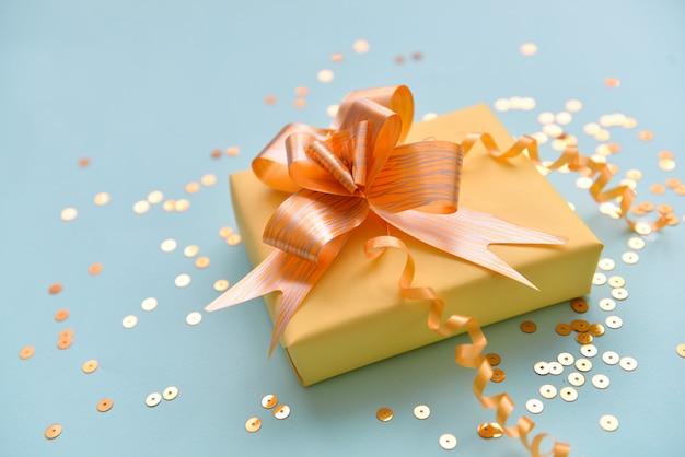 Caixa de presente com fita laranja brilhante sobre um fundo azul isolado