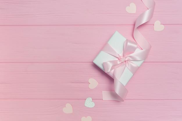 Caixa de presente com fita perto de formas de coração