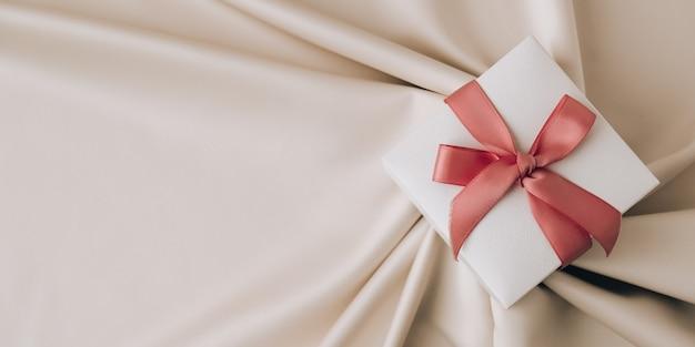 Caixa de presente com fita rosa em fundo de seda de tecido branco. vista de cima, mínima. presente. copie o espaço. fundo de férias. dia dos namorados aniversário da mulher